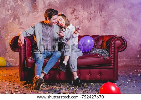 Happy young couple sitting on sofa with champagne glasses