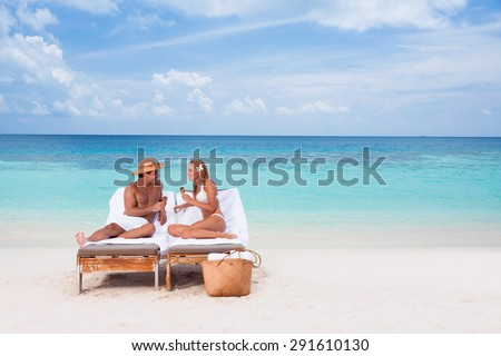 Happy young couple sitting on sunbed on the beach, eating tasty sweet cold ice cream, enjoying romantic summer vacation