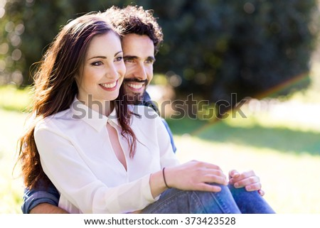 Happy young couple sitting on the grass - stock photo