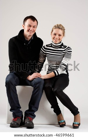 Happy young couple sitting on the white cub in studio.