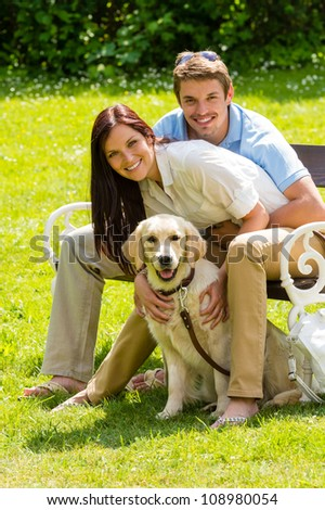 Happy young couple sitting with golden retriever dog in park - stock photo