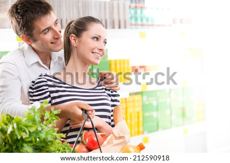 Happy young couple smiling and holding a full shopping basket at supermarket. - stock photo