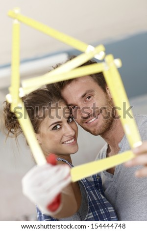 Happy young couple smiling through little house formed by ruler, DIY.