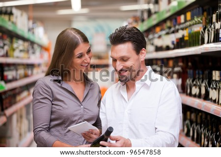 Happy young couple smiling while shopping for wine together at supermarket - stock photo
