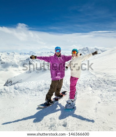 Happy young couple snowboarders in mountains of Alps - stock photo