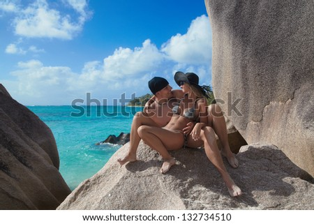 Happy young couple spending their time on stony beach at tropical island - stock photo