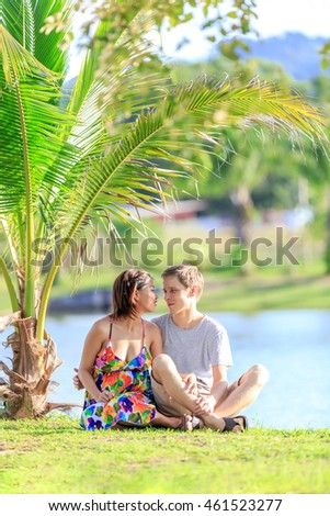 happy young couple spending time in a tropical garden on a summer day, vertical orientation