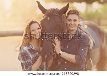 Happy young couple spending time together with their horse - stock photo