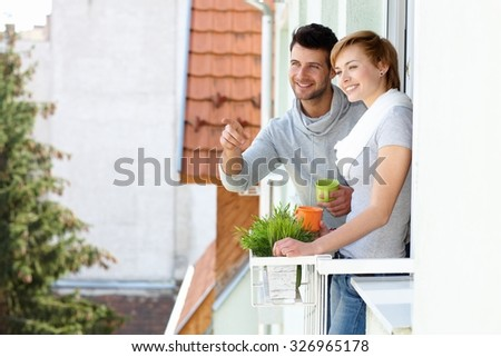 Happy young couple standing at balcony, searching distance, smiling. - stock photo