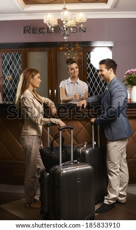Happy young couple standing at hotel reception, checking in upon arrival, smiling. - stock photo