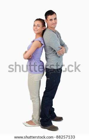 Happy young couple standing back-to-back against a white background