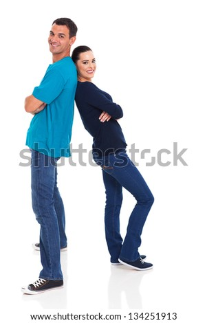 happy young couple standing back to back on white background