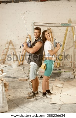 Happy young couple standing back-to-back, using power drill, renovating home, smiling, looking at camera.