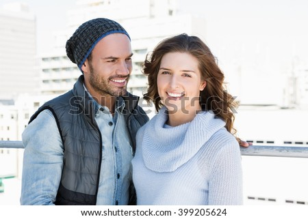 Happy young couple standing together and smiling outdoors - stock photo