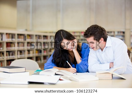 Happy young couple studying at the library - stock photo