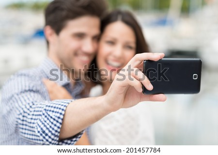 Happy young couple taking a self portrait laughing as they pose for the camera on their mobile phone, focus to the phone
