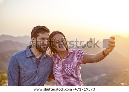 Happy young couple taking a selfie with mountains behind them while sitting on a stone wall and wearing casual clothing