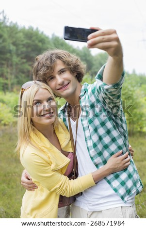 Happy young couple taking self portrait through cell phone in field - stock photo
