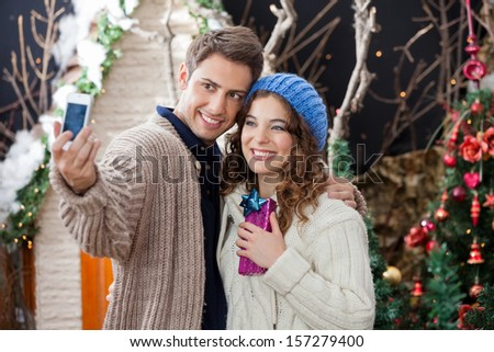 Happy young couple taking selfportrait through cellphone in Christmas store - stock photo