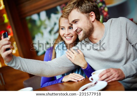 Happy young couple taking their selfie while sitting in cafe - stock photo