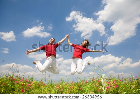 Happy Young Couple - team is jumping - stock photo