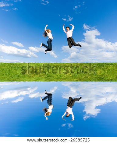 Happy Young Couple - team is jumping in the sky above a green meadow - stock photo