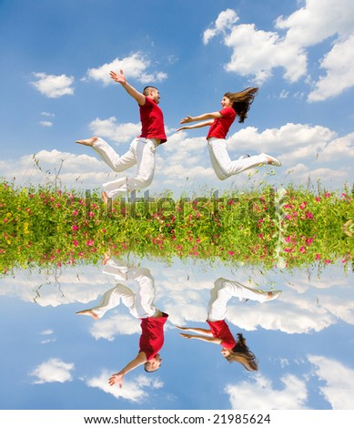 Happy Young Couple - team is jumping in the sky above a green meadow. Reflected in water - stock photo