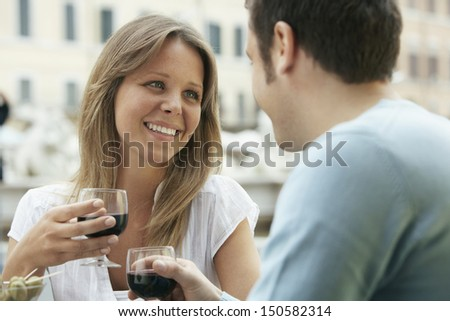 Happy young couple toasting wine glasses at outdoor cafe in Rome - stock photo