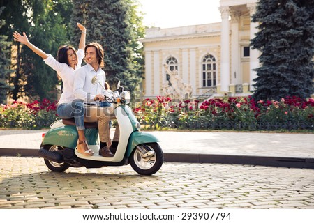 Happy young couple traveling in scooter in old european city - stock photo