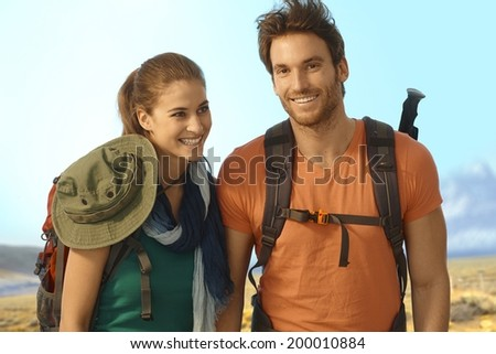 Happy young couple trekking in nice weather. - stock photo