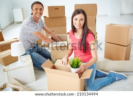 Happy young couple unpacking boxes in new flat and looking at camera