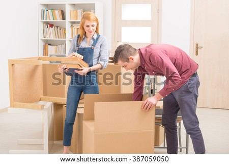 Happy young couple unpacking boxes in their new home