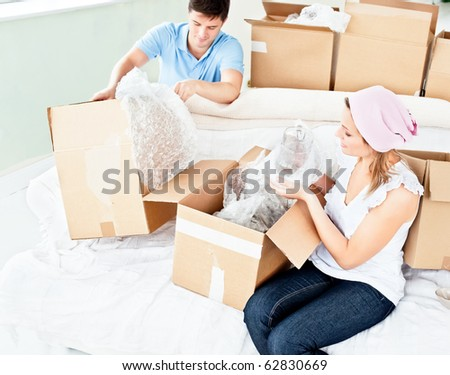 Happy young couple unpacking boxes with glasses in their new house - stock photo