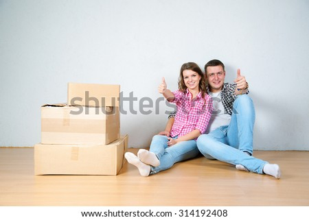 Happy young couple unpacking or packing boxes and moving into a new home. - stock photo