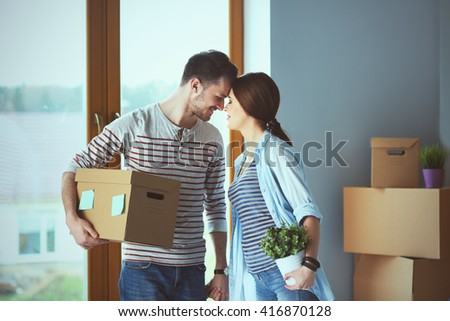 Happy young couple unpacking or packing boxes and moving into a new home - stock photo