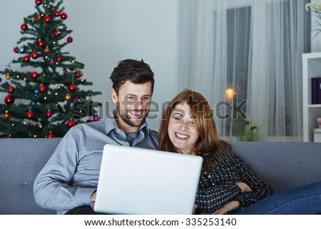 happy young couple use or watch something on laptop pc for christmas on sofa - stock photo