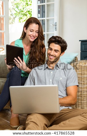 Happy young couple using digital tablet and laptop in living room