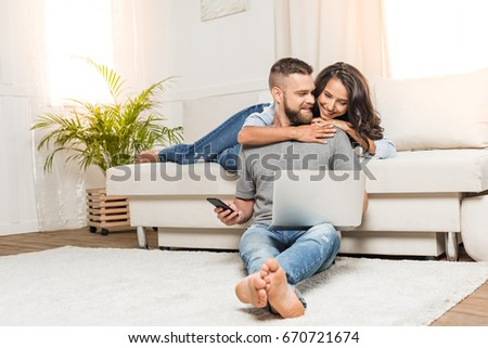 Happy young couple using laptop and smartphone while sitting together at home