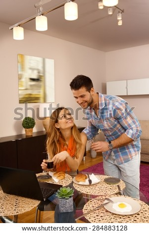 Happy young couple using laptop computer at home while having breakfast, smiling. - stock photo