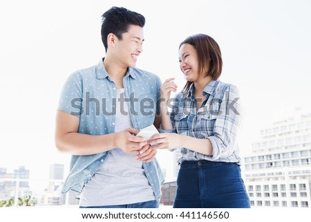 Happy young couple using mobile phone and smiling outdoors - stock photo
