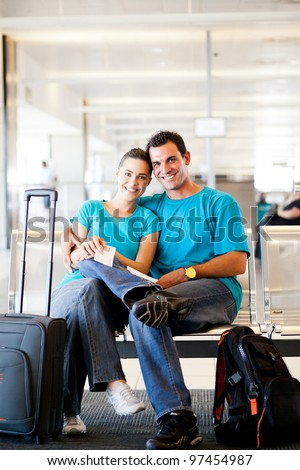 happy young couple waiting for flight at airport