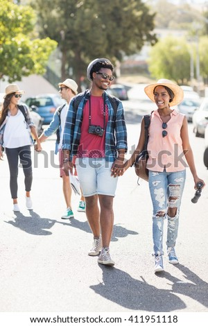 Happy young couple walking hand in hand on road - stock photo