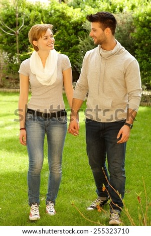 Happy young couple walking outdoors hand in hand, smiling. Full size. - stock photo