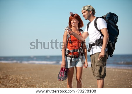 happy, young couple walking together on a deserted beach, wearing backpacks. the man points to a place next to them
