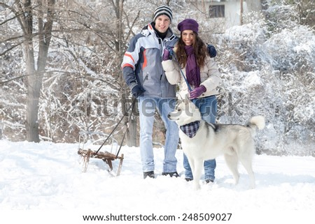 Happy young couple walking with dog snowy forest