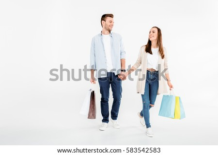 Happy young couple walking with shopping bags and looking at each other isolated on white