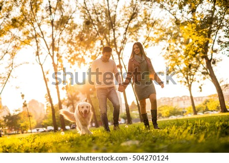 Happy young couple walking with their dog.