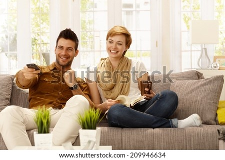 Happy young couple watching tv at home. - stock photo