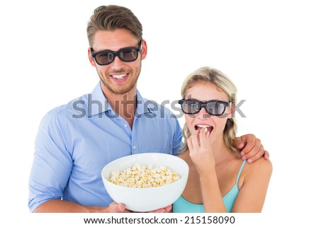 Happy young couple wearing 3d glasses eating popcorn on white background - stock photo