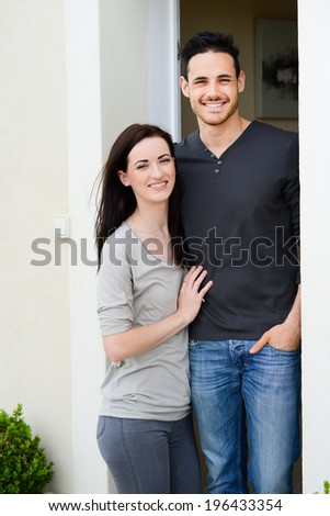 happy young couple welcome in their new house showing the door house keys - stock photo